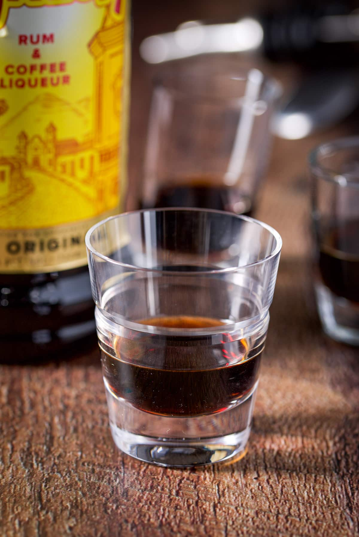 A beveled glass in front with Kahlua in it with the other glasses and bottles in the background