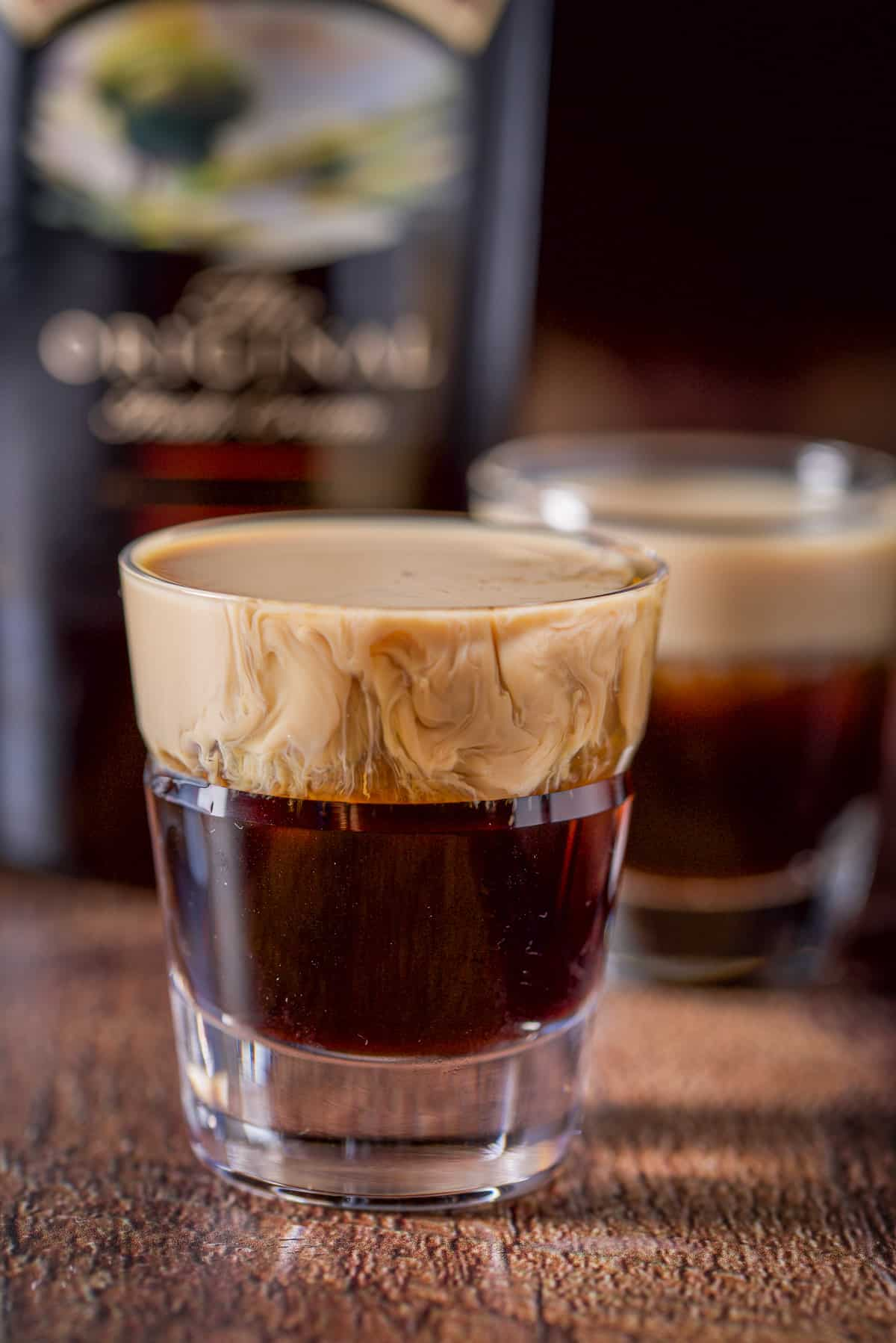 Baileys layered into the beveled glass with another glass and the bottle in the background