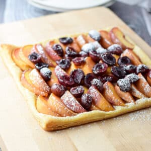 A board with cherries and peaches on a puff pastry - square