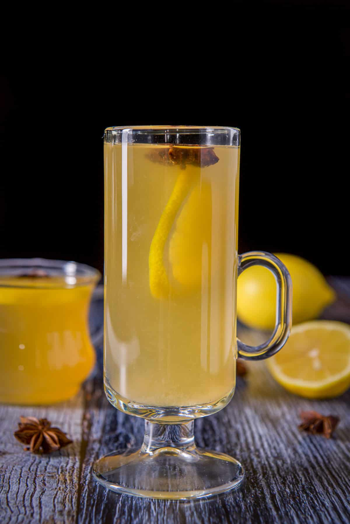 Tall glass mug in front of the shorter one, both filled with the lemon cocktail, star anise and lemon wheels for garnish