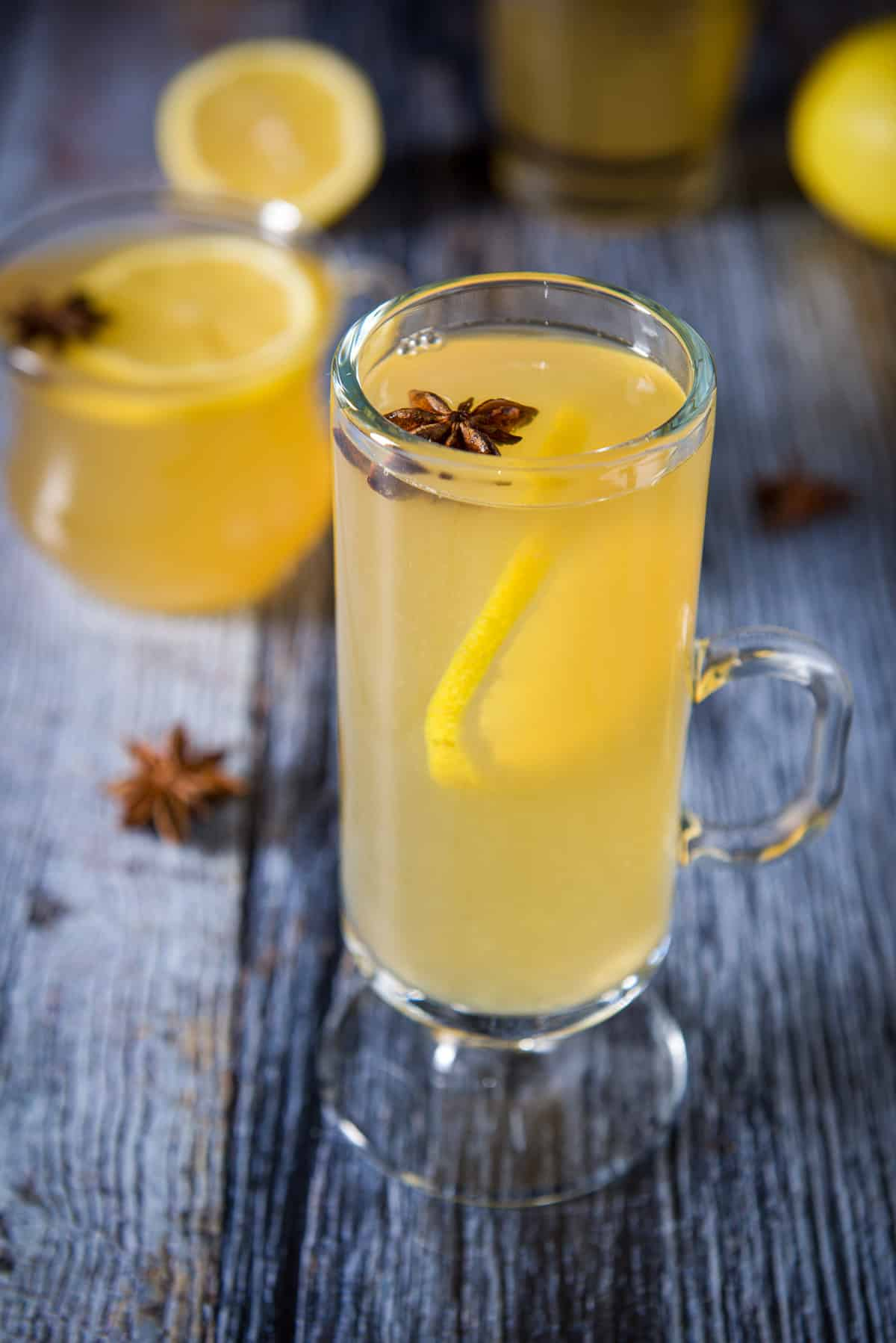 A tall glass mug with the golden cocktail with the smaller mug in the background. The cocktails are garnished with star anise and lemon wheels
