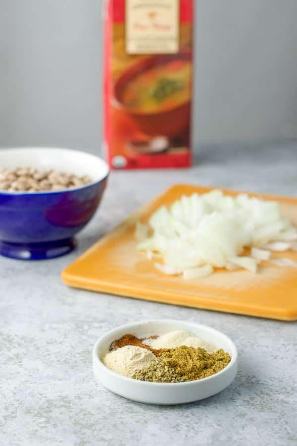 Oregano, cumin, garlic powder, onion powder and chili powder on a dish, with onions chopped, beans in a bowl and broth