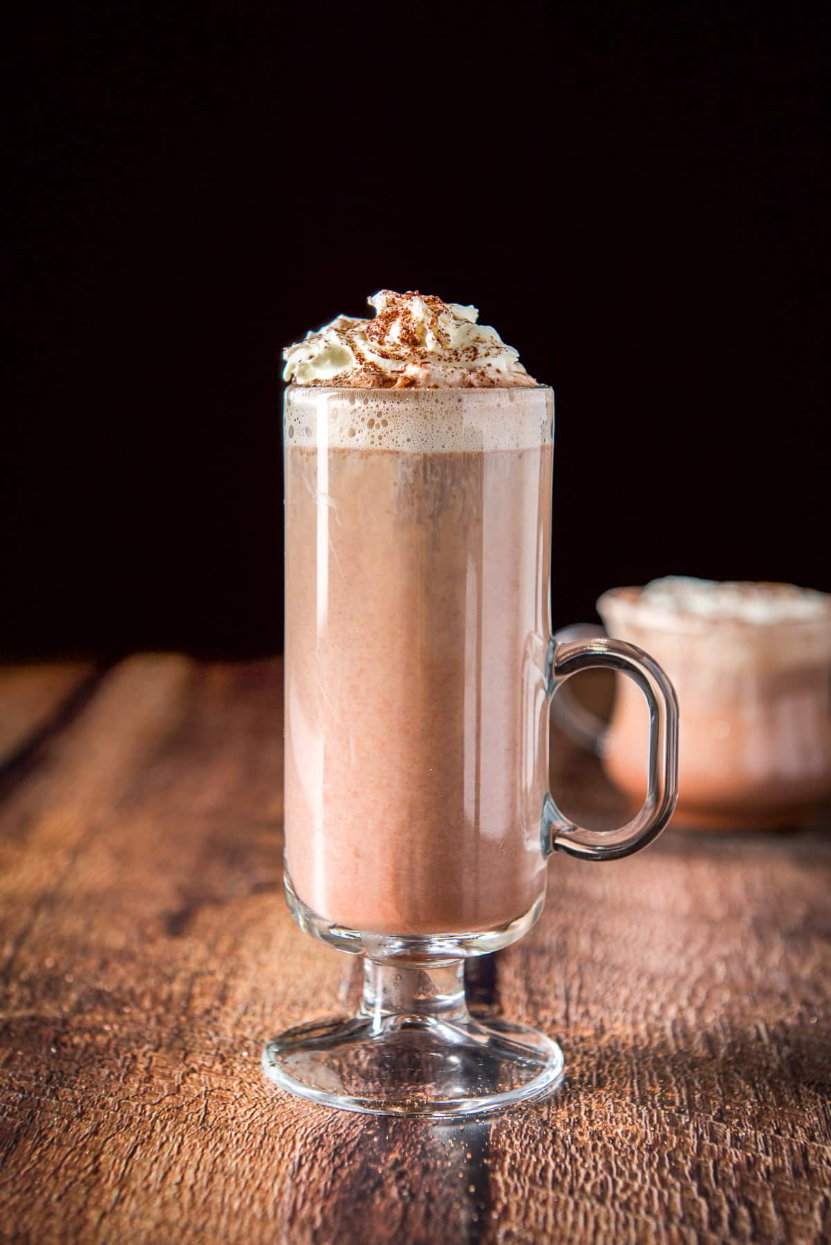 Vertical view of the tall mugh with the chocolate drink, whipped cream and cocoa on top