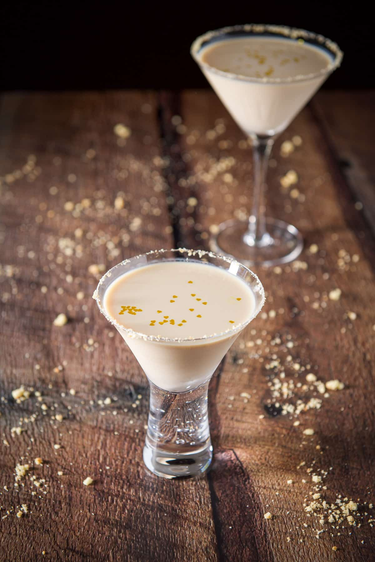 A short bubble glass with the cream drink with gold hearts floating in it. There is another glass and cookie crumbs on the table