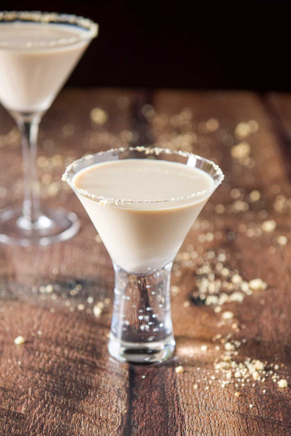 A small bubble glass garnished with cookie crumbs and the cream drink in it. There is a classic martini glass and cookie crumbs on the table behind it