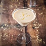 A classic martini glass garnished around the rim with sugar cookie crumbs. Inside the glass is a cream drink with little gold hearts floating - square
