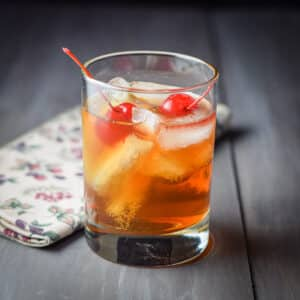 A double old fashioned glass filled with the Manhattan with two cherries in it - square