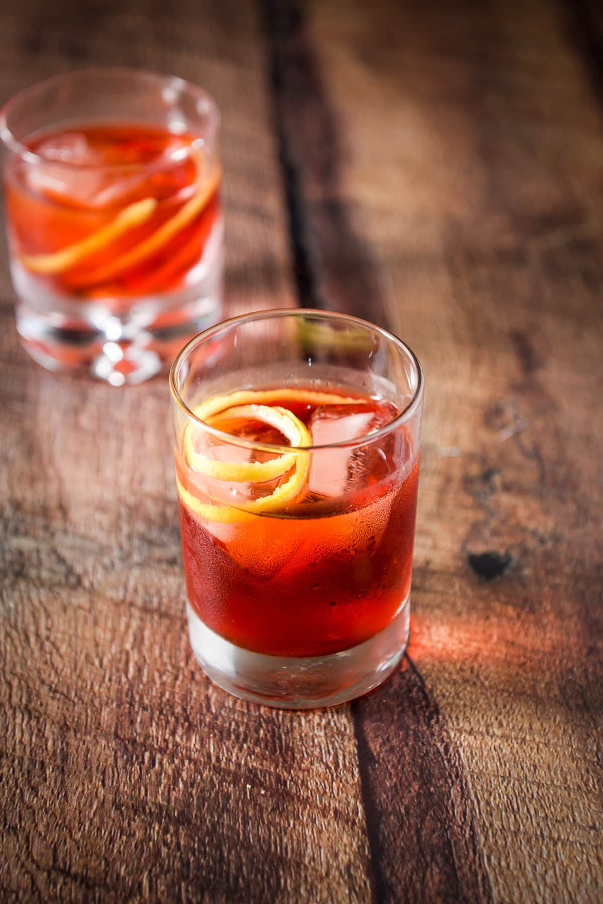 The taller double old fashioned glass filled with the negroni with the twist as garnish