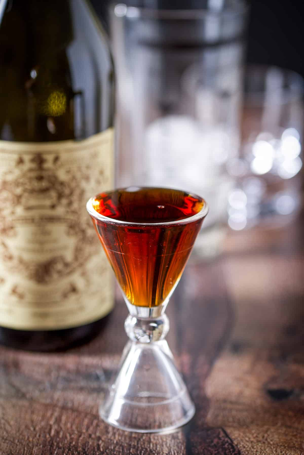 Sweet vermouth measured out with the bottle and ice filled shaker in the background