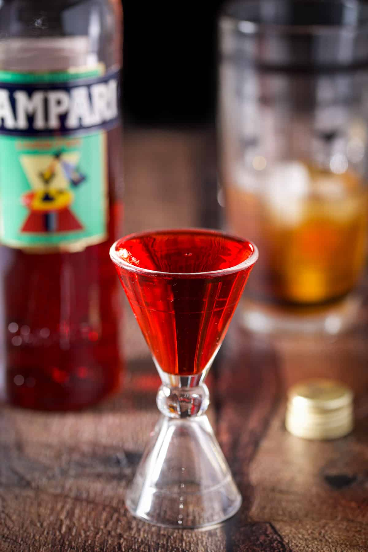 Campari measured out with the bottle and shaker in the background