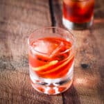 A bubble glass filled with the red cocktail with a twist in it - square