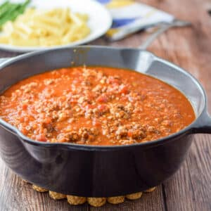 Gravy in a cast iron pan with a white plate with pasta in the background - square