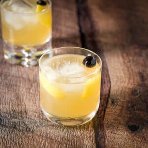 Two classes with golden cocktails with lemon twists and maraschino cherries - square