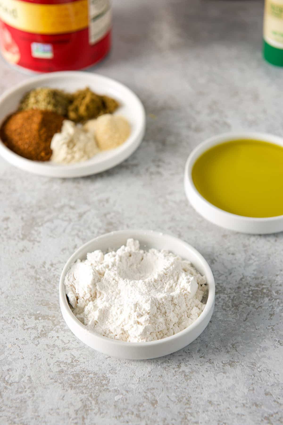 Flour, olive oil, spices and herbs in small white plates