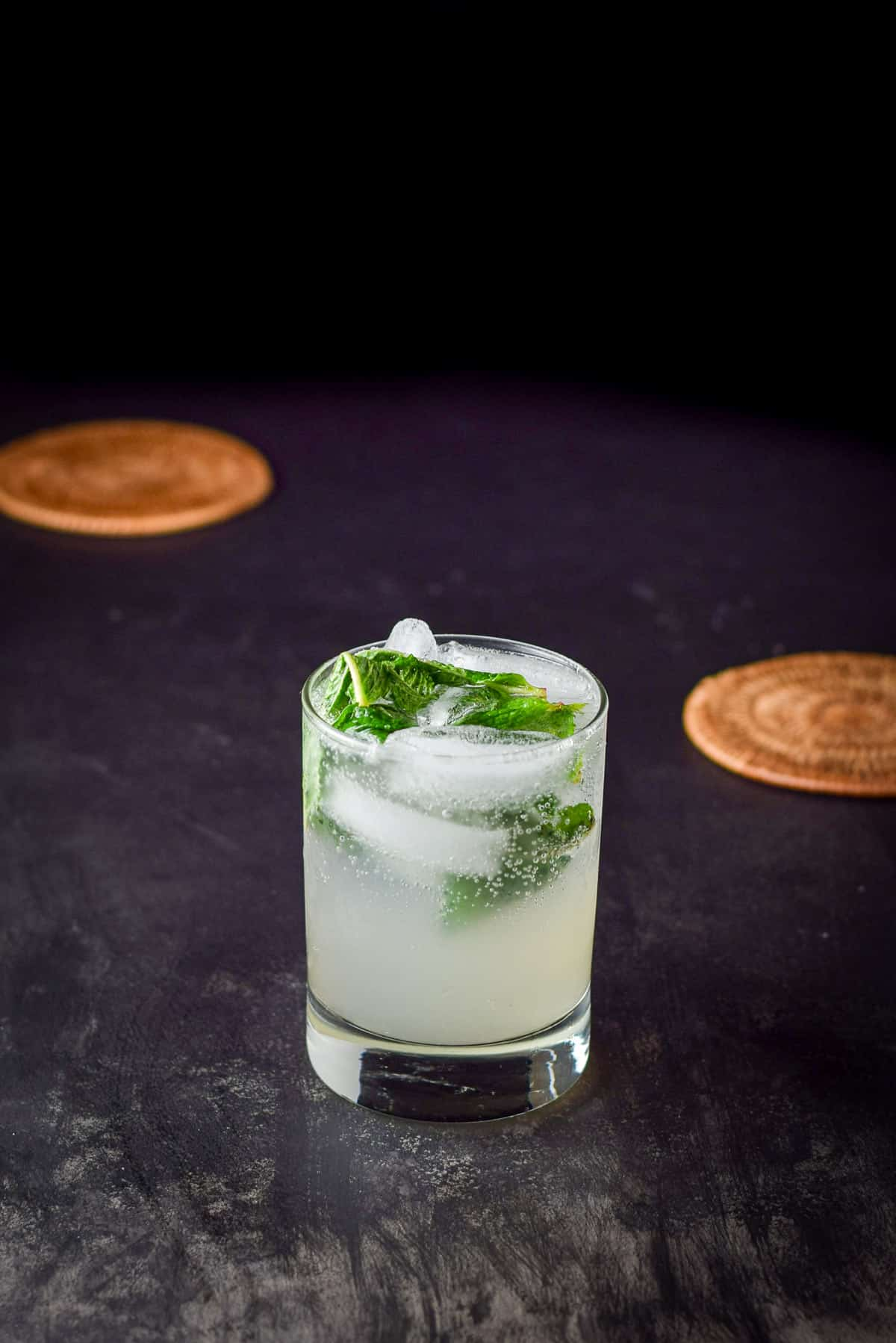 A double old fashioned glass filled with a mojito with mint floating in it
