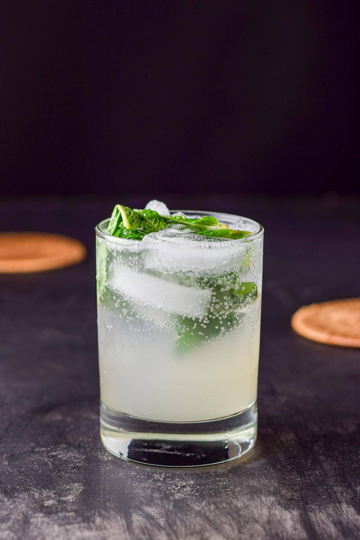 A ginger and grapefruit mojito on a black table with coasters in the background