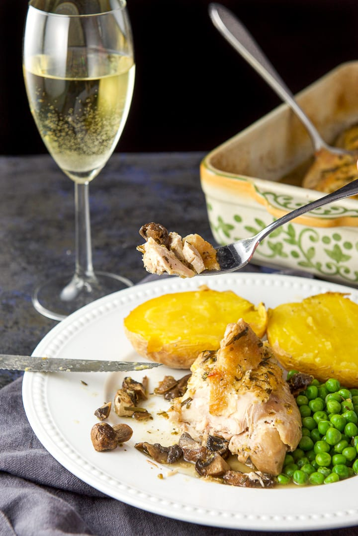 A fork with chicken on it held over the plate with wine and the baking dish held in the background