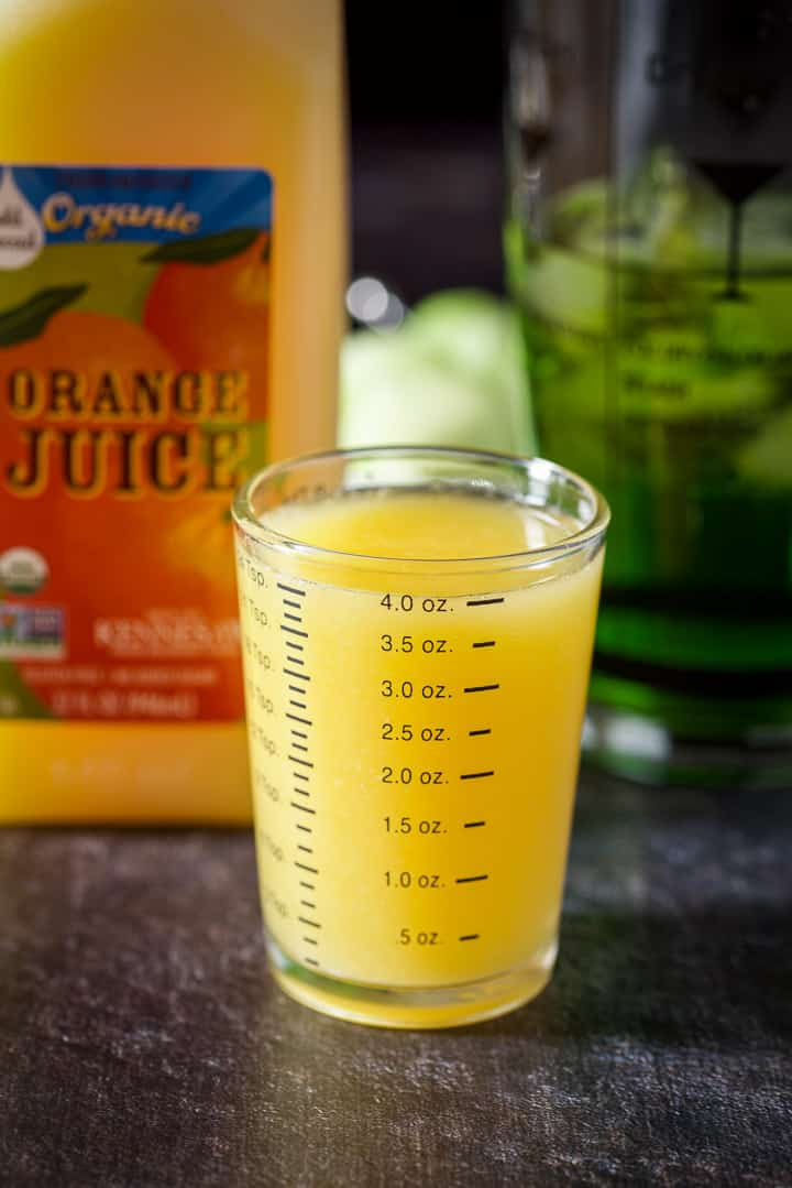 Orange juice measured out with the carton and shaker in the background