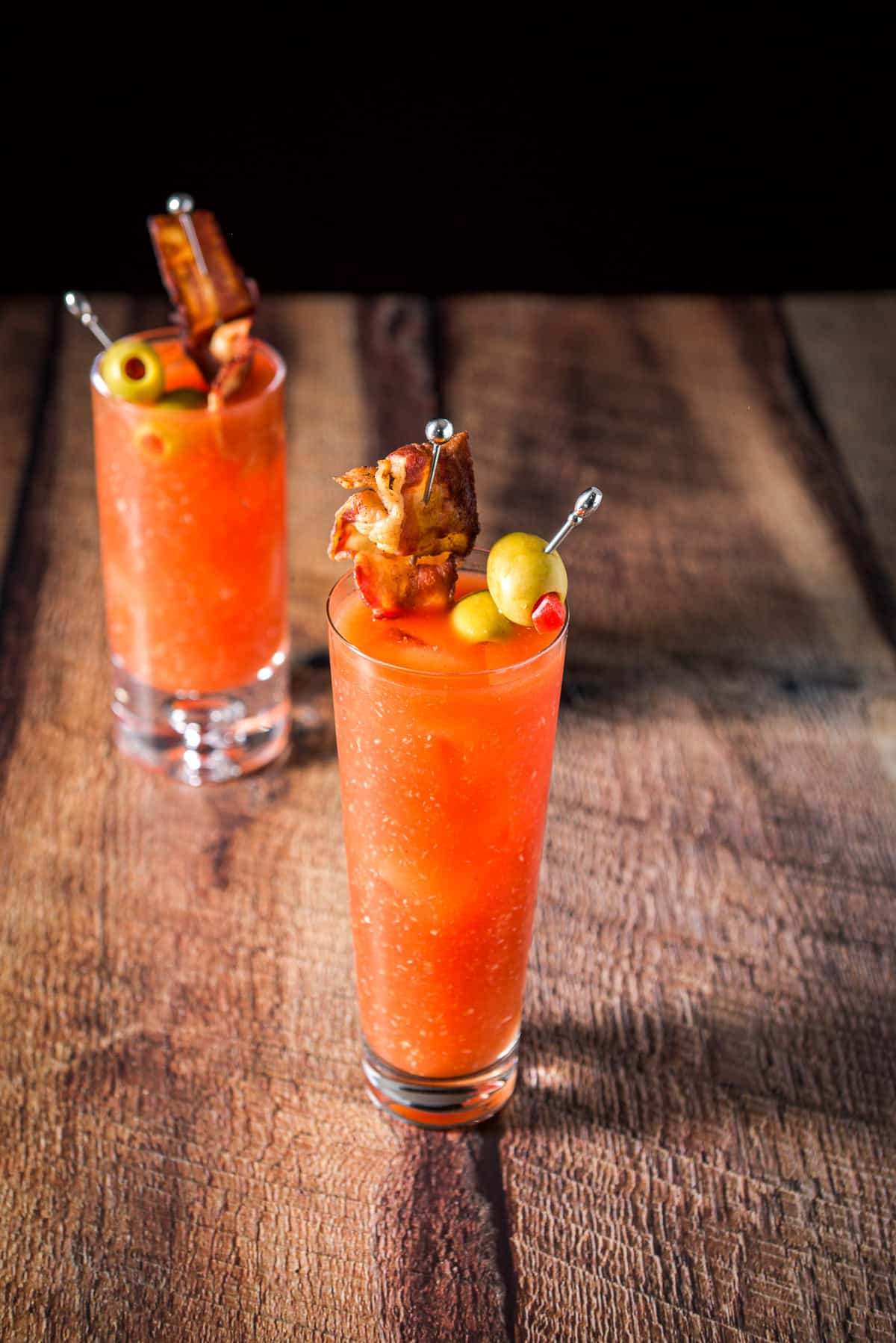 Two tall glasses with the bloody mary in them with garnish on picks