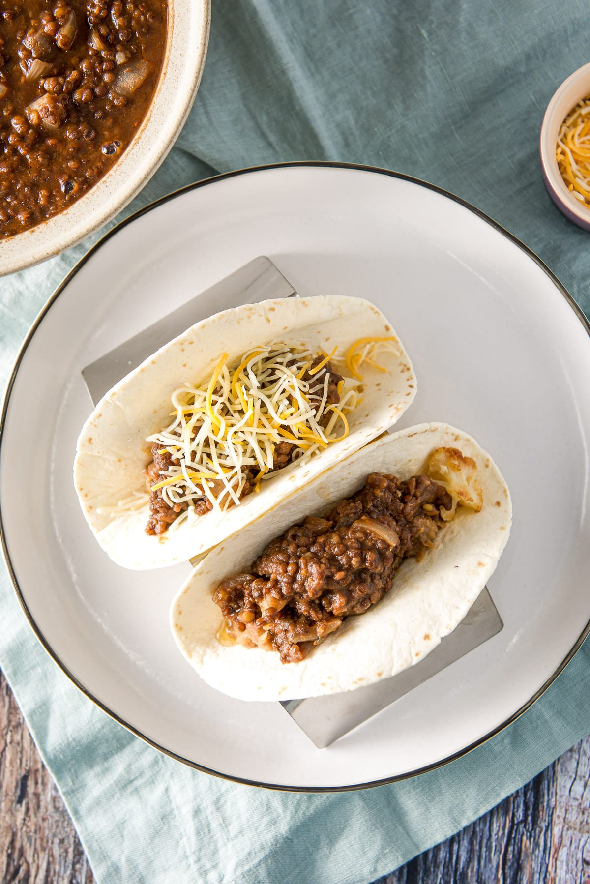 Overhead view of a plate with two tacos on it with lentils off the the side