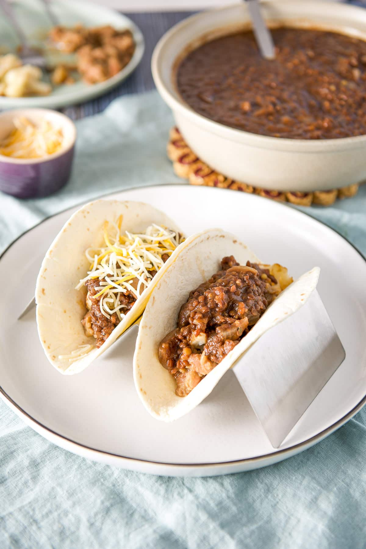 A white plate with a taco holder with flour tortillas and the taco filling in it along with a bowl of lentils in the back