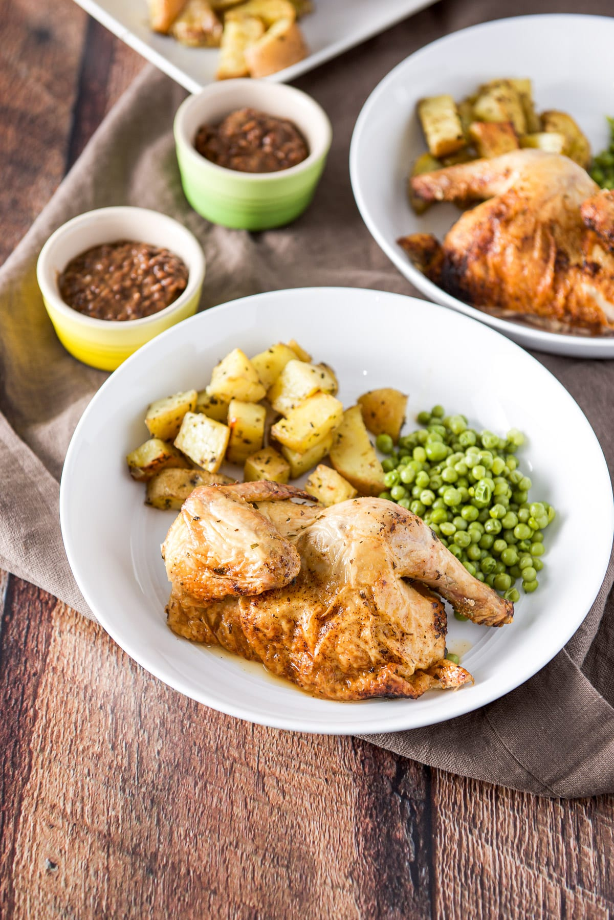 A deep white plate with half of a hen on it with potatoes and peas