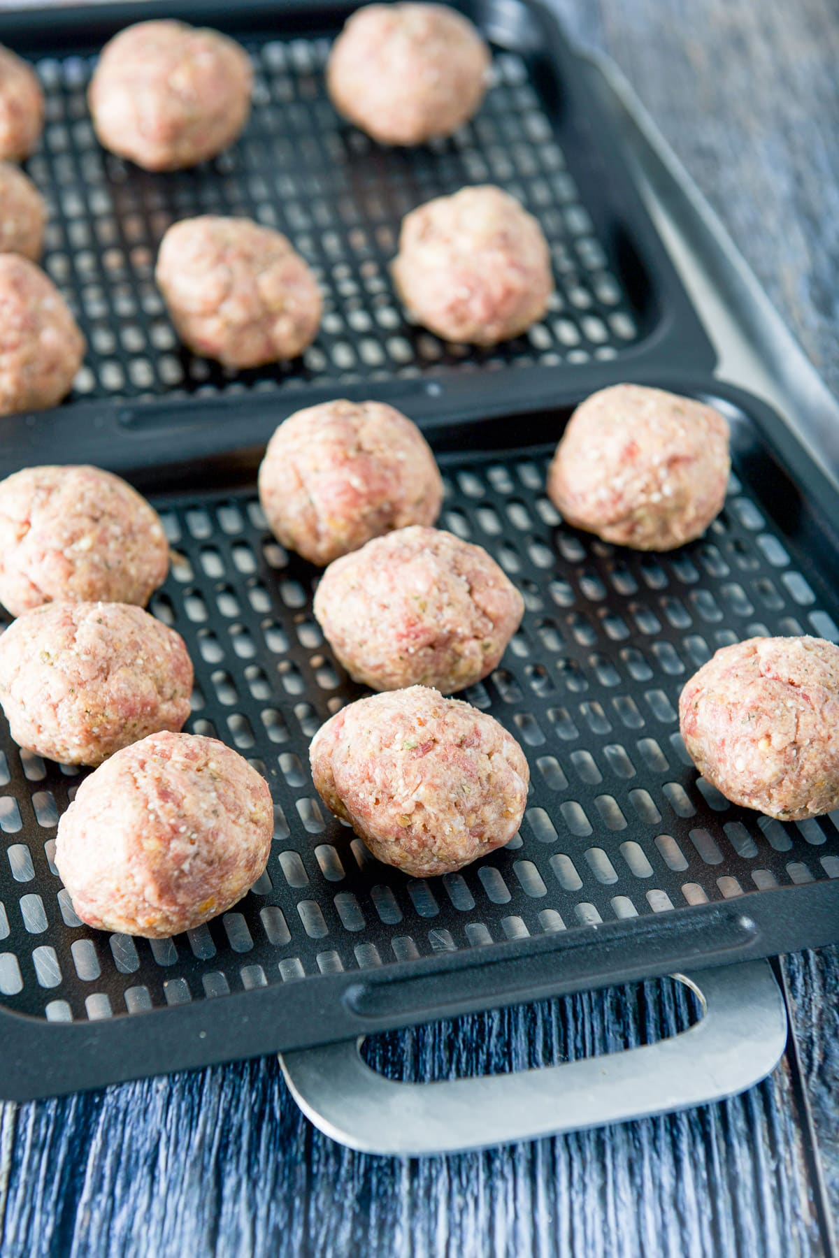 Raw meat rolled into balls on two grill trays