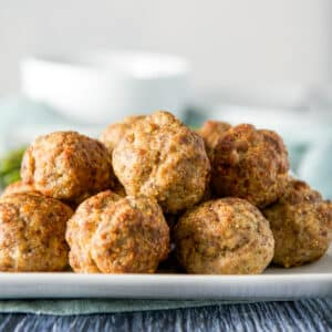 A white plate with a pile of meatballs on it - square