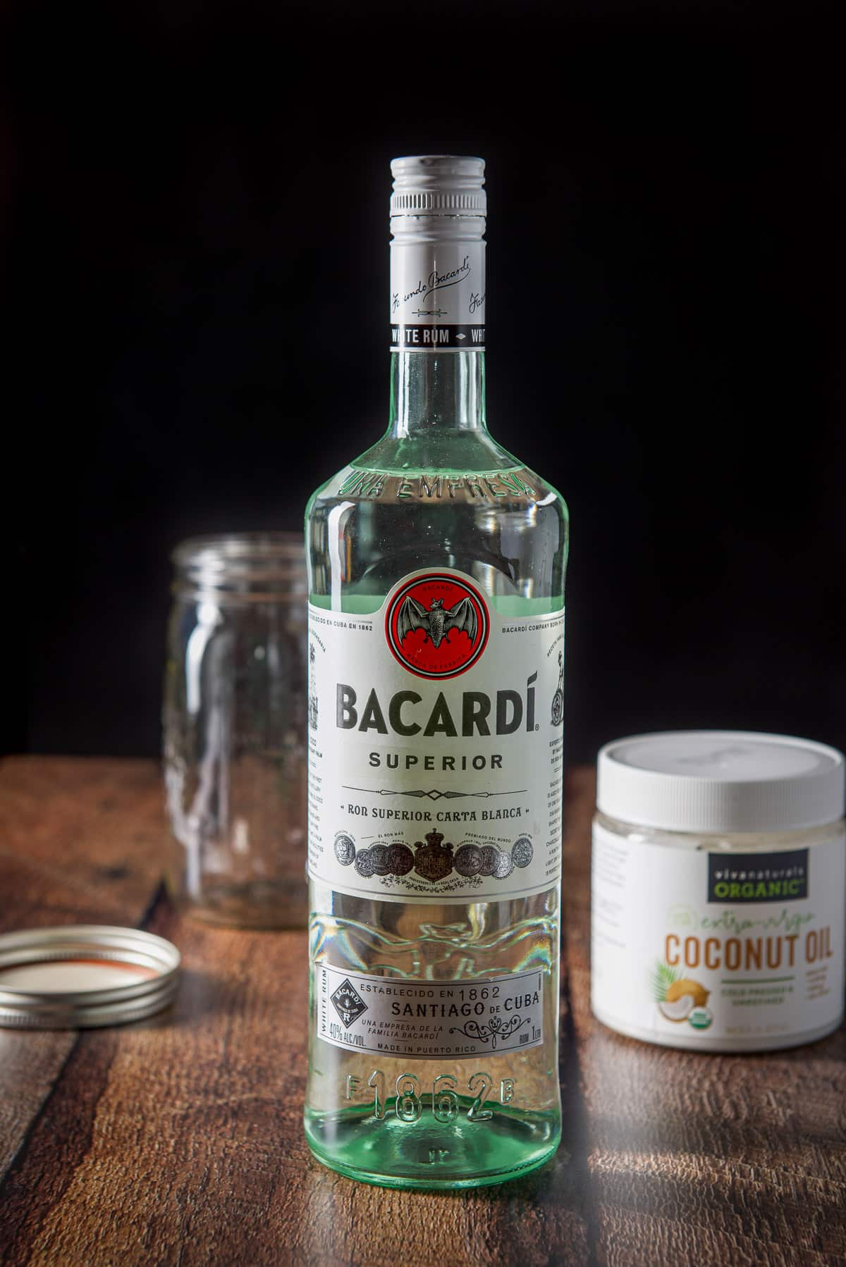 Rum, coconut oil and a jar and lid on a wooden table