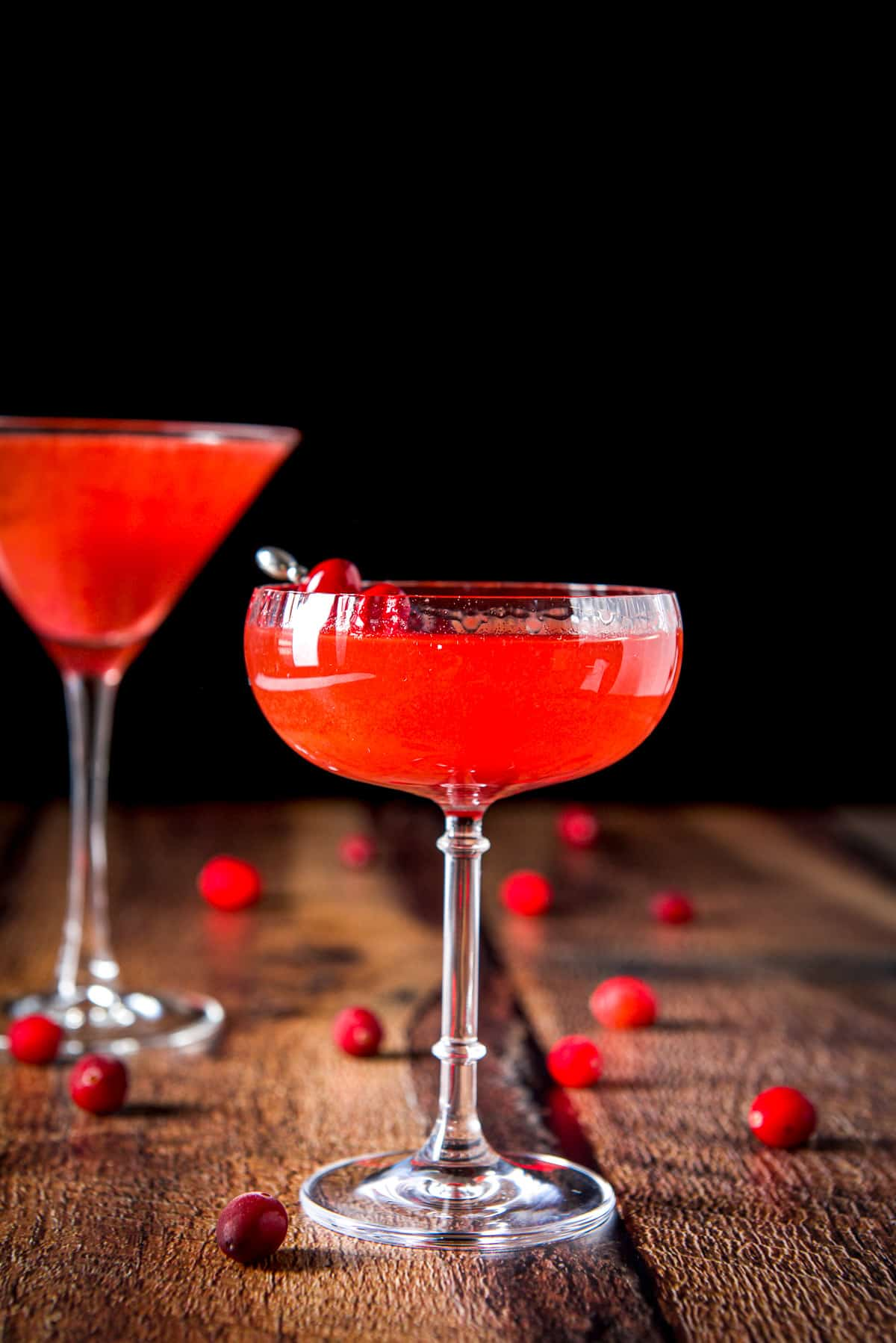 Vertical view of the beveled coup with the cranberry drink with cranberries strewn on the table and another martini glass in the background