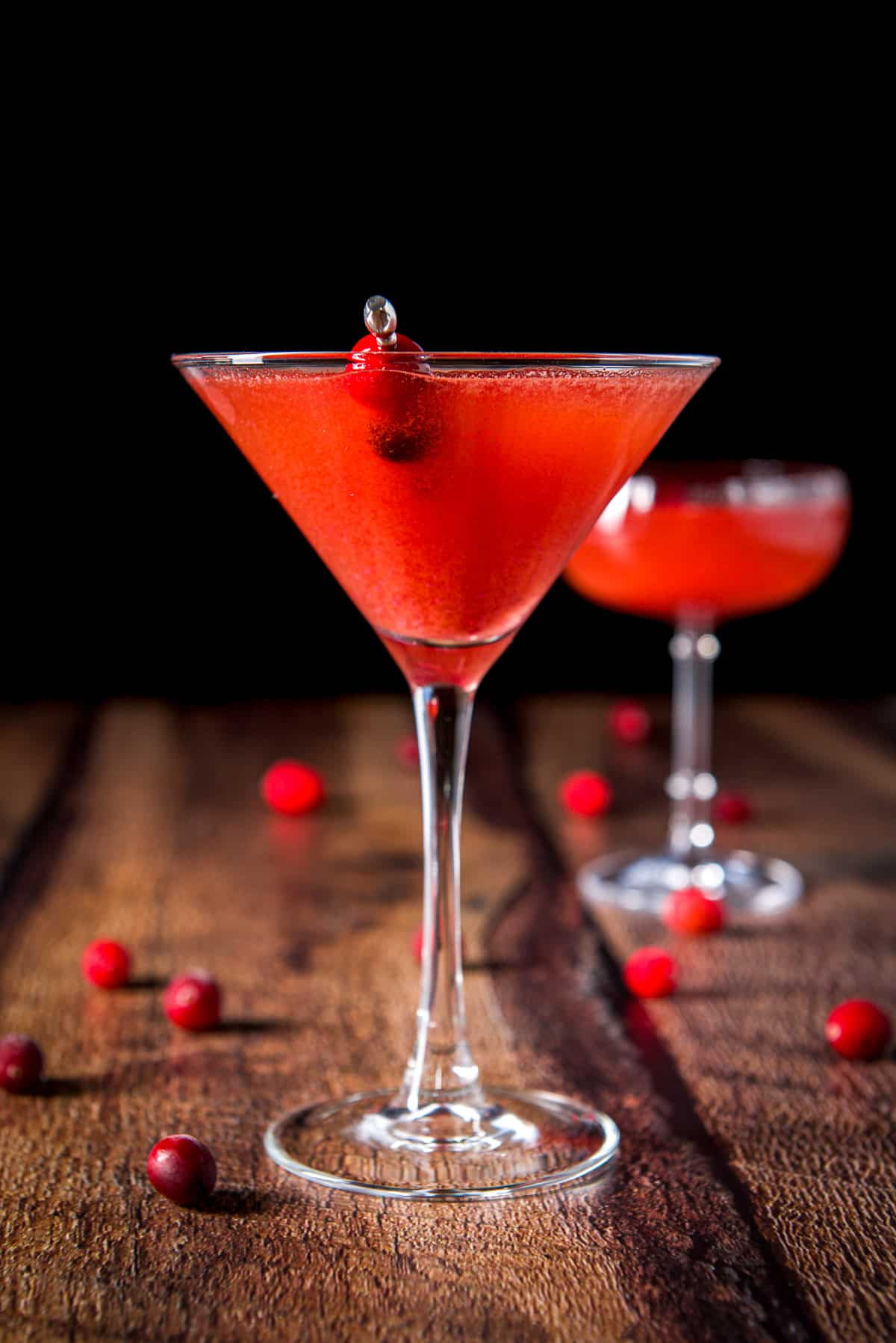 Classic martini glass with the red cocktail in it along with cranberries on a pick