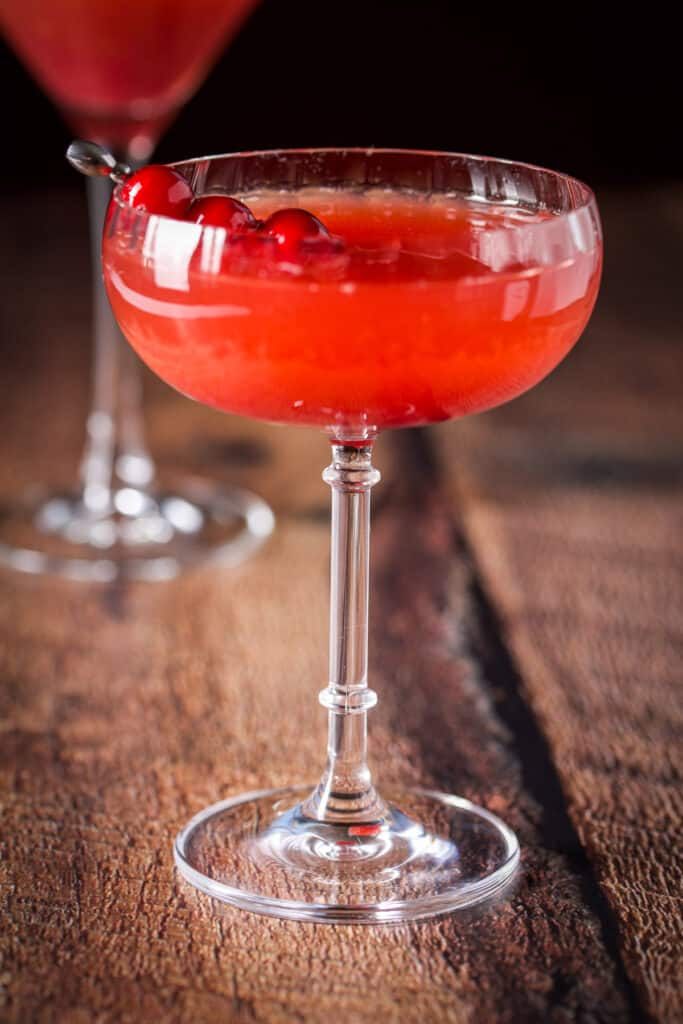 A cranberry martini in a coupe glass with cranberry garnish on a pick