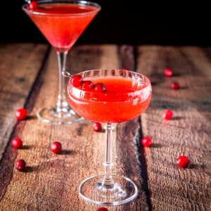 A beveled coupe glass filled with a cranberry cocktail. there are cranberries on the table and a classic martini glass in the back - square