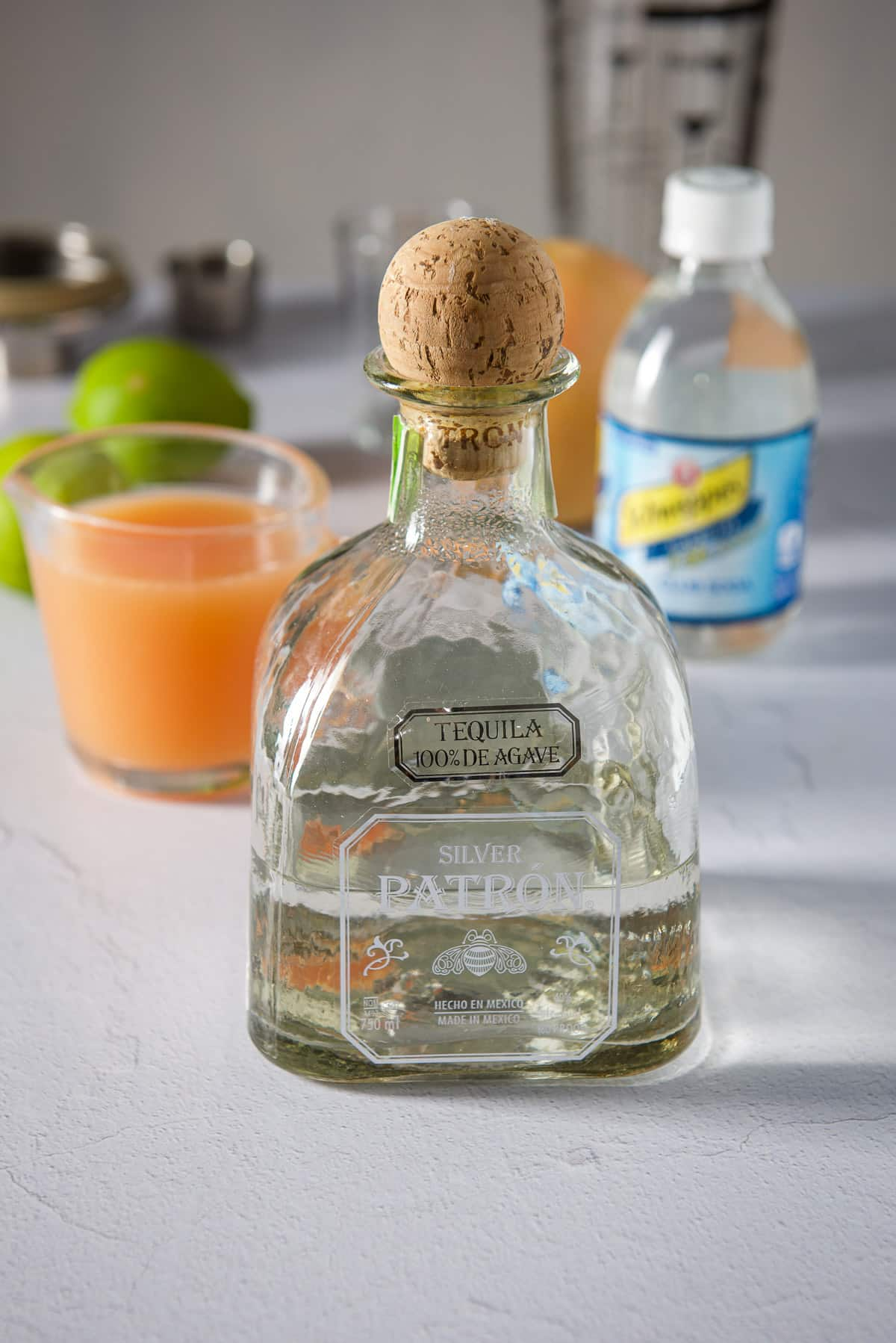 Tequila, grapefruit juice, limes, club soda, a grapefruit and shaker in background