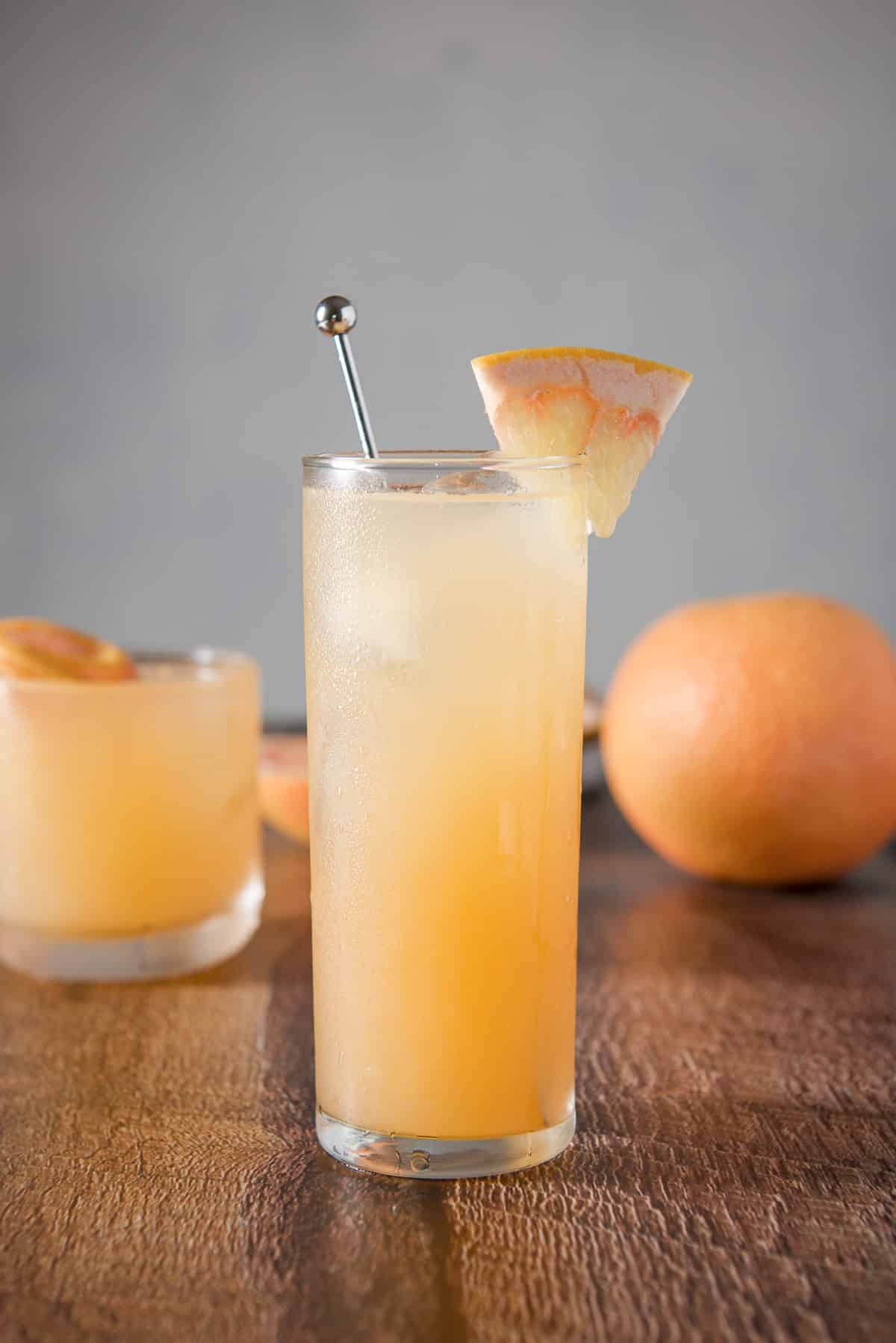 Vertical view of the tall collins glass with the cocktail with a stirrer and wedge of grapefruit. There is a shorter glass in the background and a whole grapefruit
