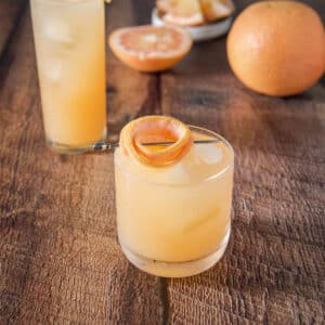 Glass with a grapefruit garnish on the side of the glass with a big grapefruit and slices in the background - square