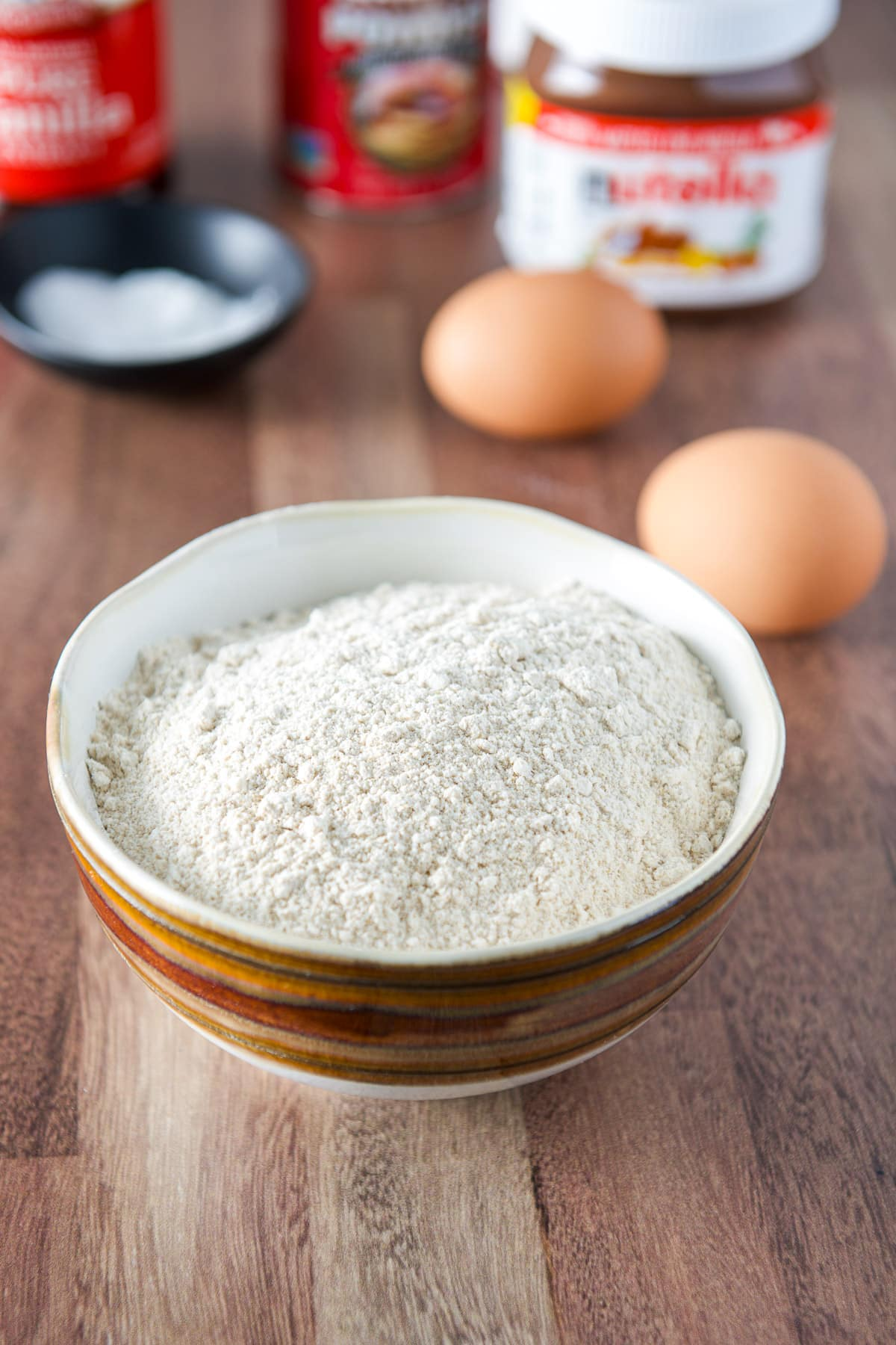 A brown bowl of flour, two eggs, Nutella, baking soda and powder