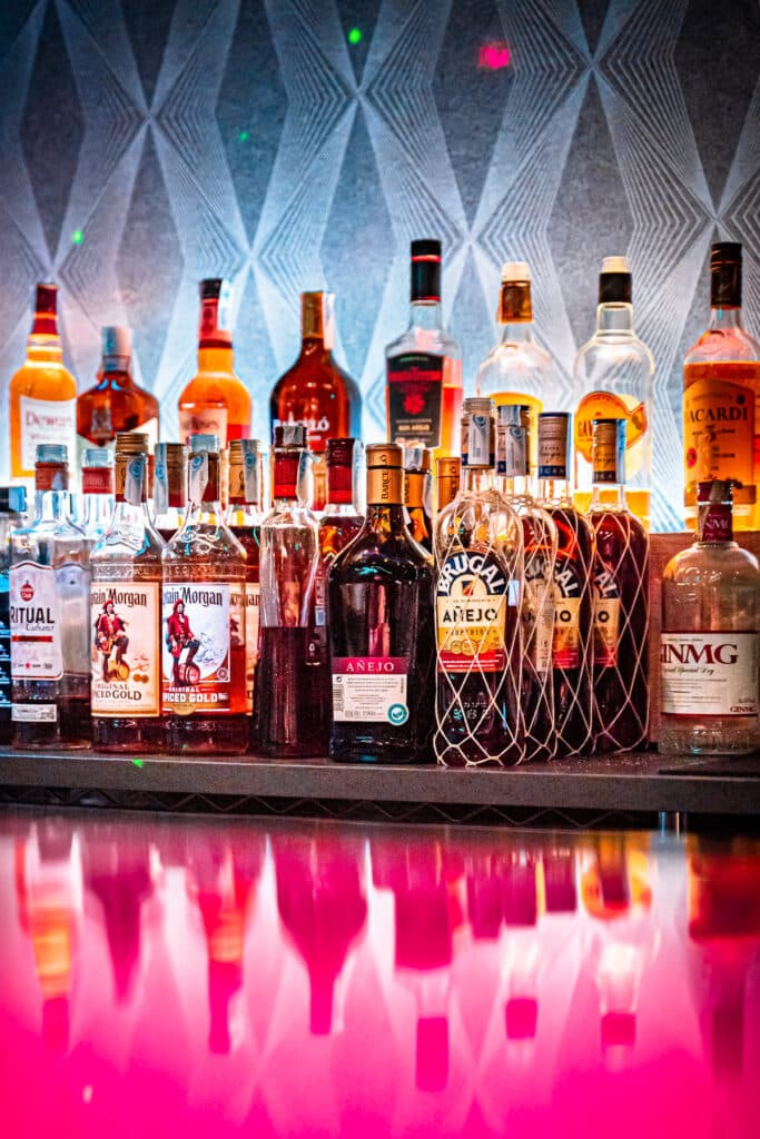 A bunch of alcohol bottles lined up with a vibrant pink table