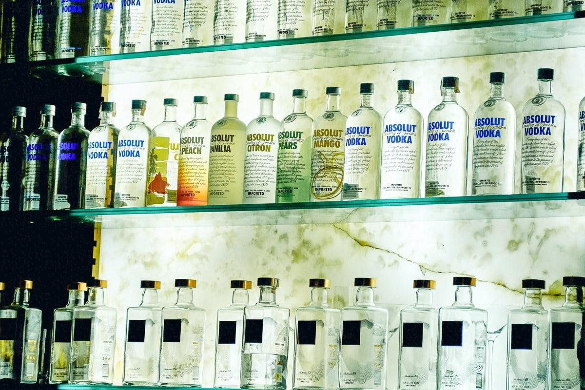 Three shelves holding multiple vodka bottles