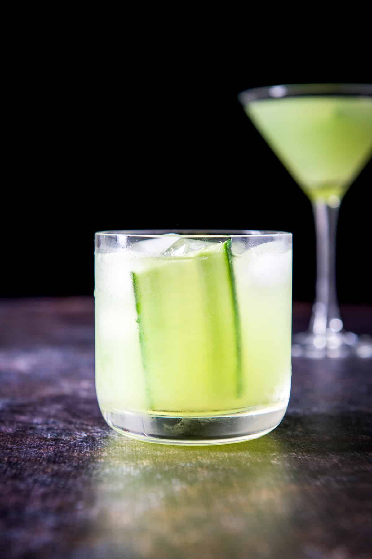 The cucumber gimlet in a double old fashioned glass with the classic martini in the back. There is a cucumber slice in it as garnish