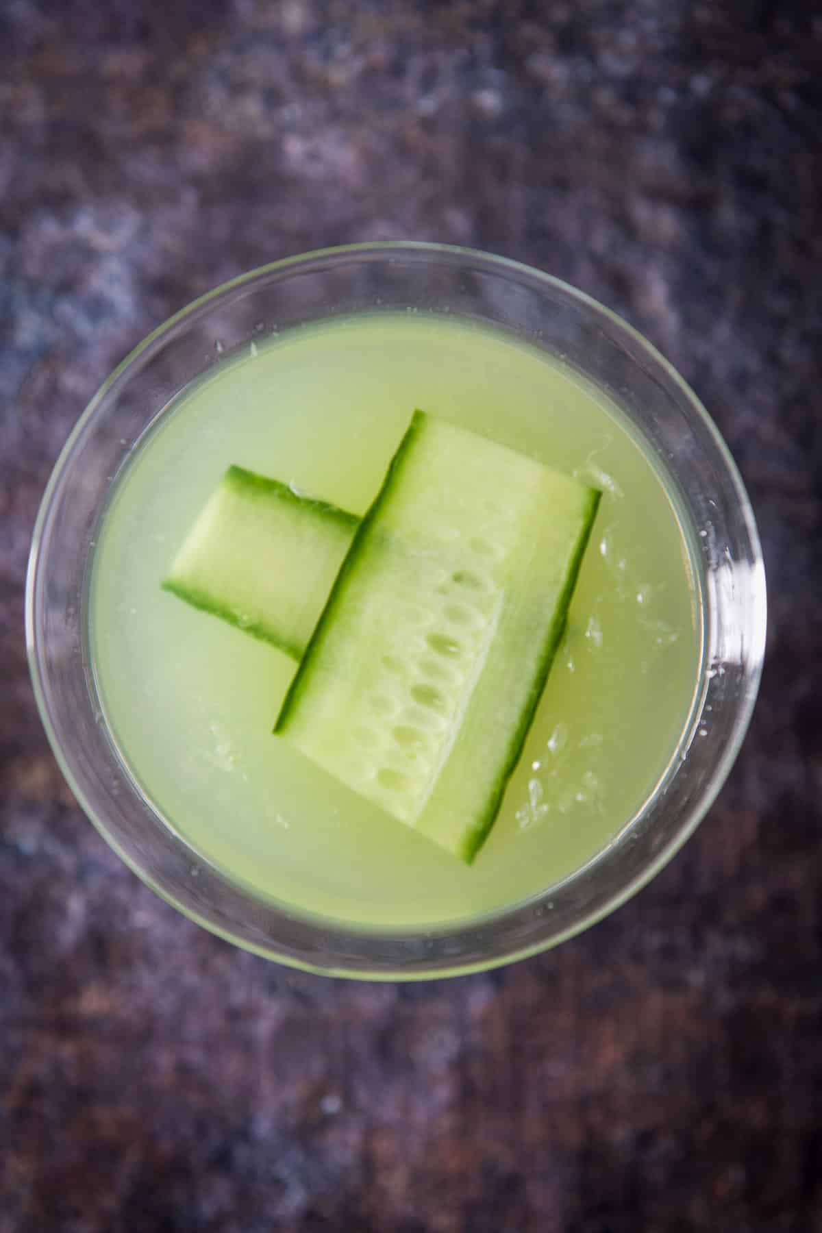 Overhead view of a green cocktail in a martini glass with two strips of cucumber floating