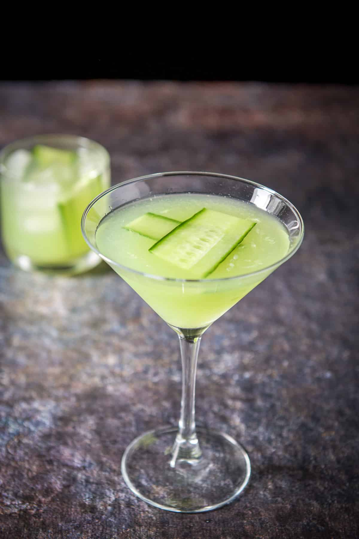A classic martini glass filled with the cucumber cocktail with a double old fashioned glass in the back