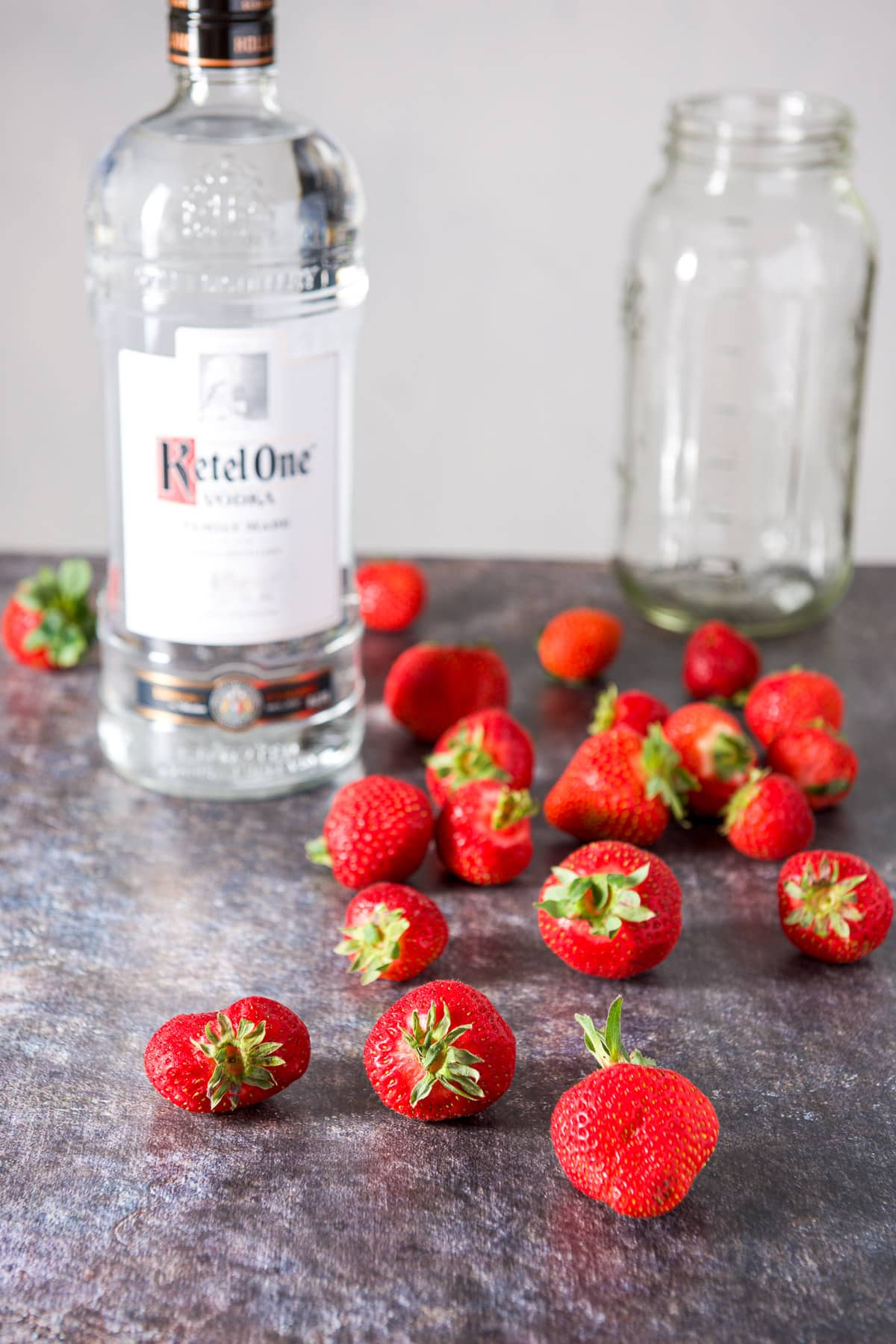 Strawberries on a table with a bottle of vodka along with a large jar
