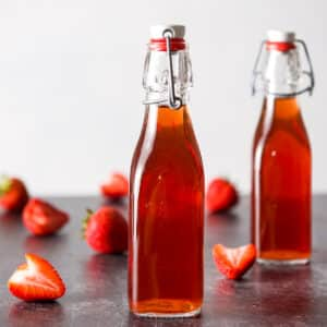 Two bottles with strawberry vodka with strawberries on the table - square