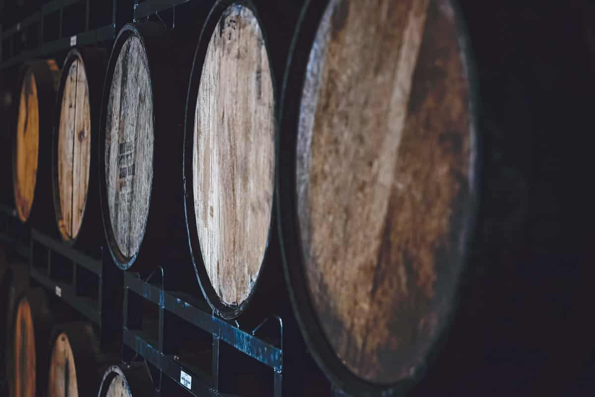 Rows of whiskey filled casks on metal shelves - square