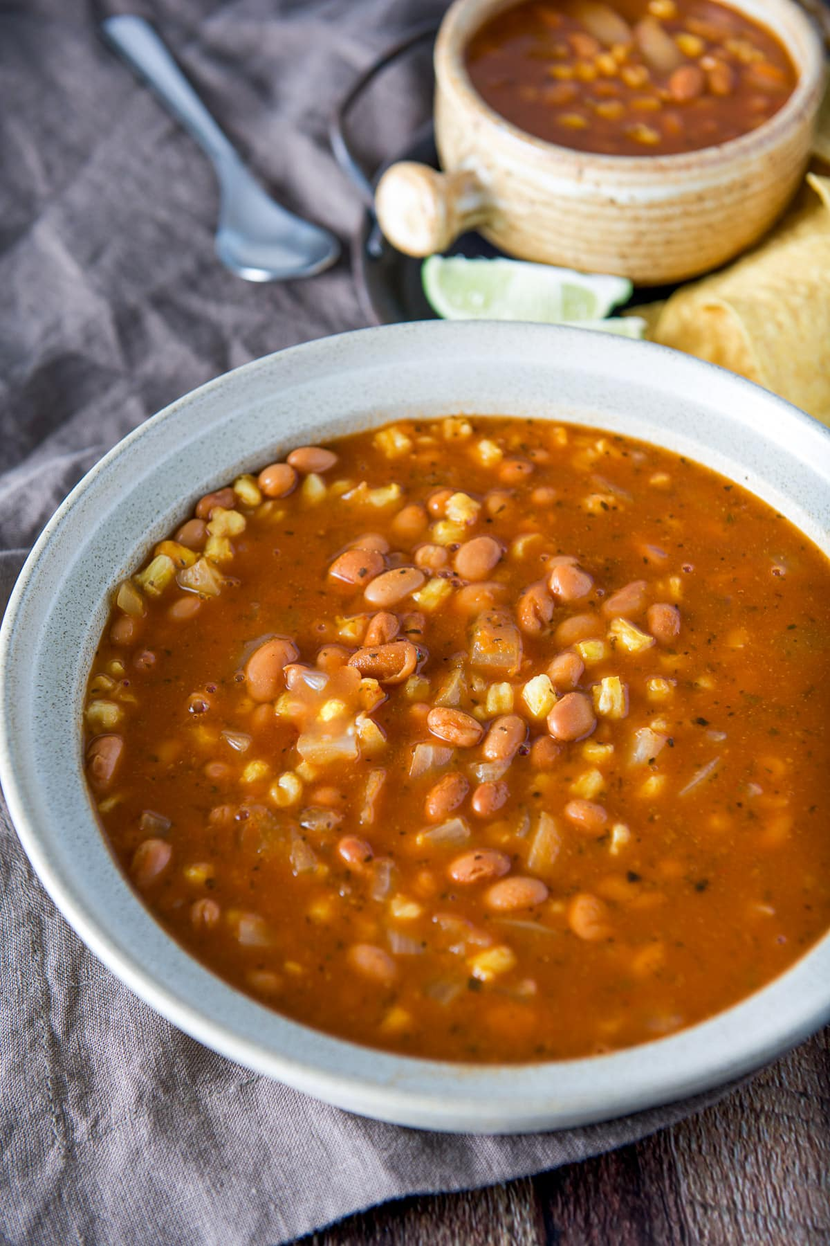 A big bowl with the posole soup in it, with a crock full of the soup in the back