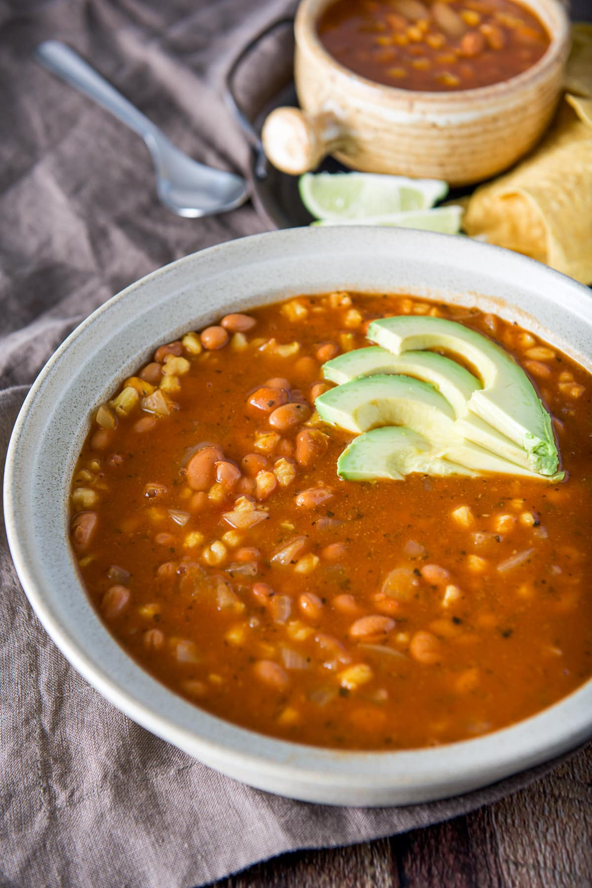 A big bowl with the bean and hominy soup with sliced avocados on top and a crock in the back