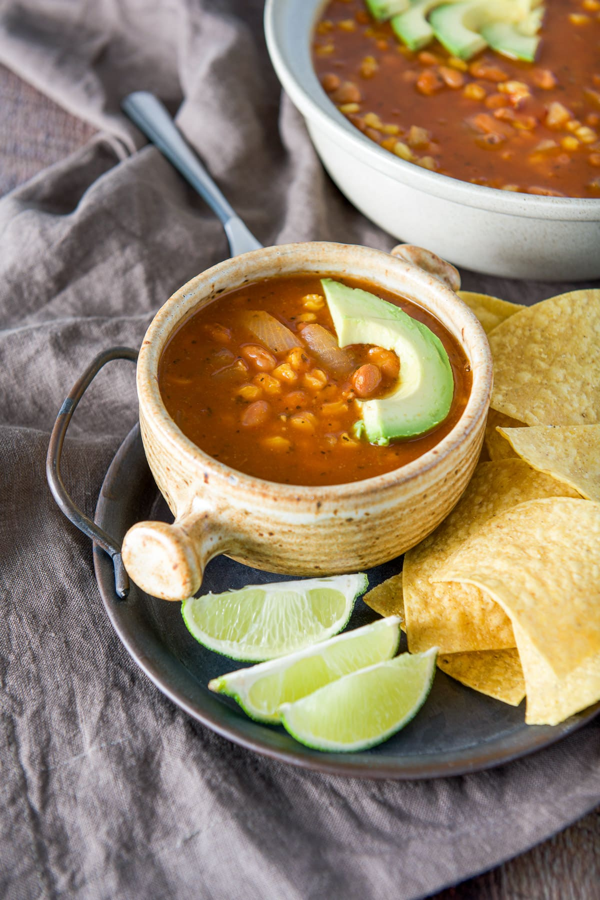 A tray with chips, lime wedges and a crock of soup with an avocado slice on top