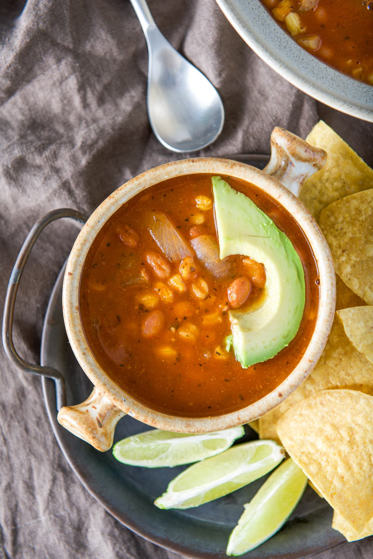 Overhead view of the soup in a crock with avocado, lime wedges and chips