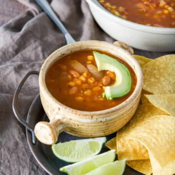 A tray with chips, lime wedges and pozole in a crock with a slice of avocado on it